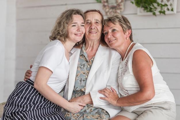 Oma; mutter und tochter umarmen sich und lächeln, während sie zu hause auf der couch sitzen Kostenlose Fotos