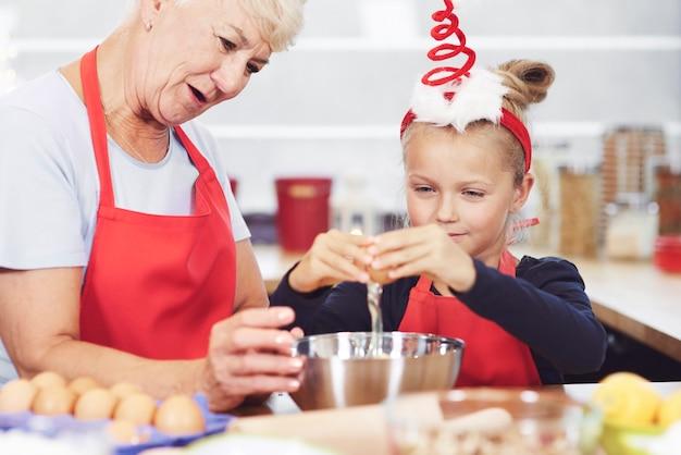 Oma und enkelin bereiten snack in der küche vor Kostenlose Fotos