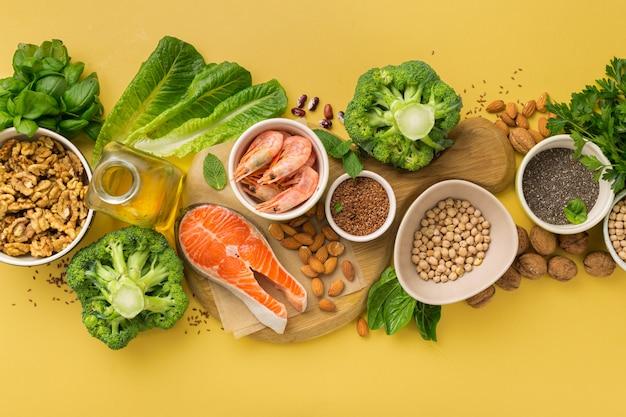 Omega 3 nahrungsquellen und omega 6 auf gelbem hintergrund draufsicht. lebensmittel mit hohem fettsäuregehalt, einschließlich gemüse, meeresfrüchten, nüssen und samen Premium Fotos