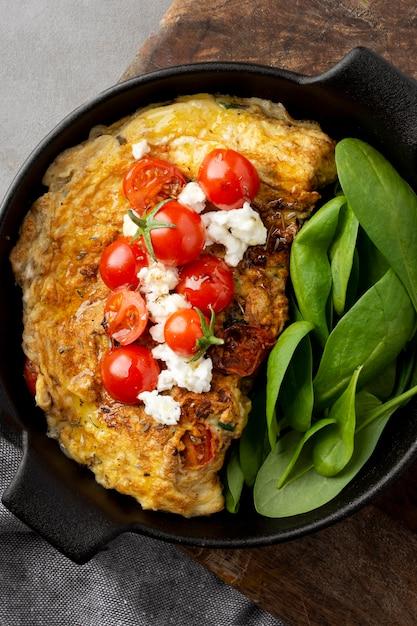 Omelett der draufsicht mit blättern und tomaten Kostenlose Fotos