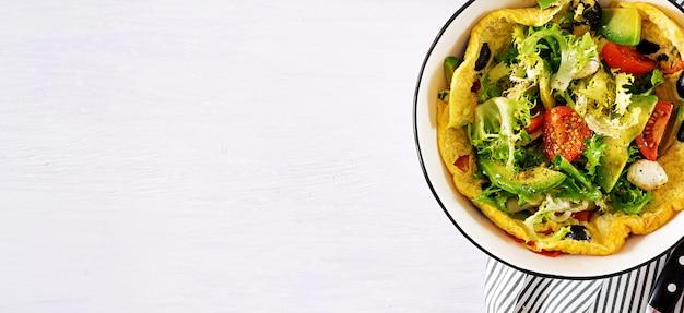 Omelett mit frischen tomaten, schwarzen oliven, avocado und mozzarella. Premium Fotos