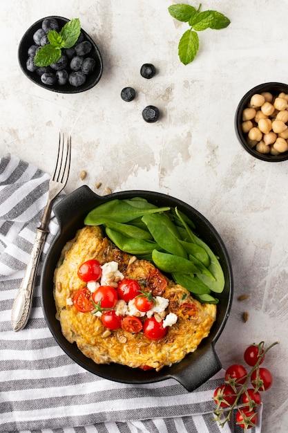 Omelett mit käse und tomaten mit besteck Kostenlose Fotos