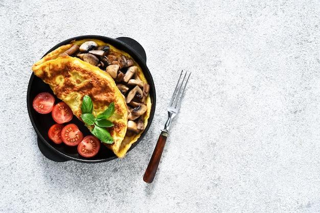 Omelett mit pilzen und tomaten zum frühstück Premium Fotos