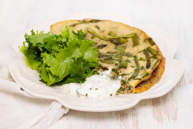 Omelett mit spargel, frischem salat und sauce auf weißem teller Premium Fotos