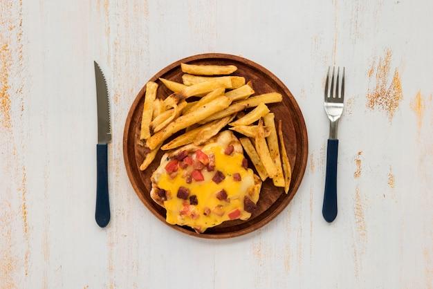 Omelett und pommes-frites auf hölzernem brett auf schmutz malten schreibtisch Kostenlose Fotos