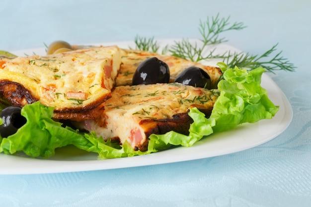 Omelettscheiben auf einem teller Premium Fotos