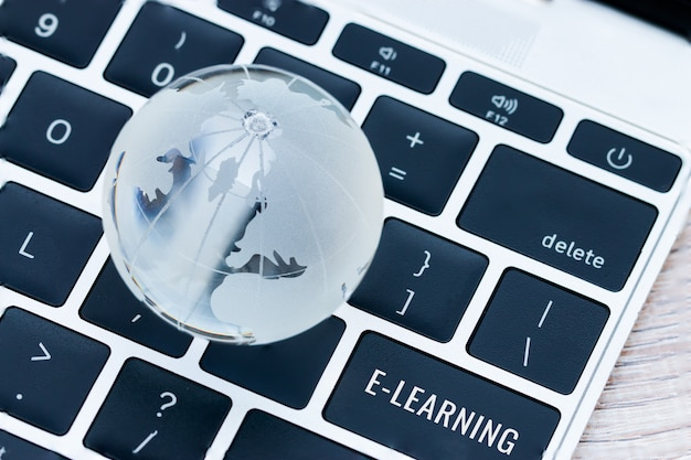 On-line-lernbildung durch technologiekonzept, wörter, die an e-learning sind, tragen schlüsselknöpfe des computerlaptops ein Premium Fotos