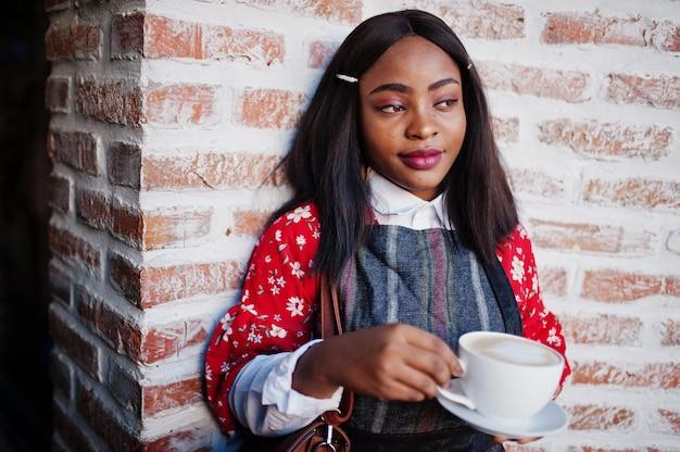 Ð¡onfident junge afroamerikanische frau in der intelligenten freizeitkleidung im café mit tasse heißem getränk in der hand. Premium Fotos