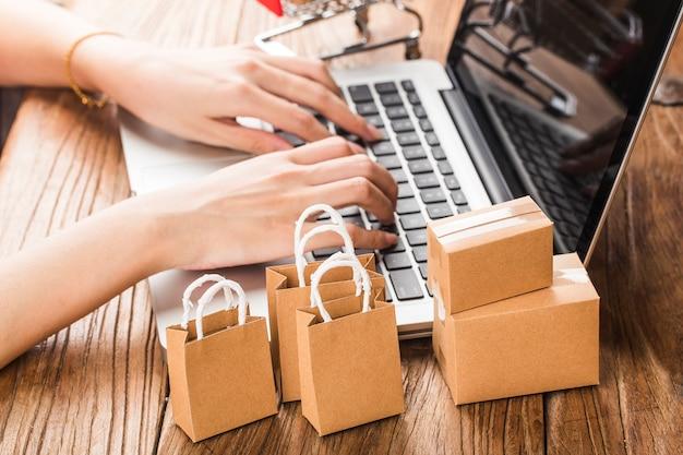 Online kaufen zu hause konzept. kartons in einem einkaufswagen auf einer laptoptastatur. Premium Fotos