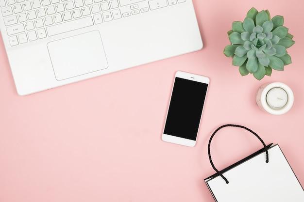 Online-shopping-konzept. frauenhände mit telefon und laptop auf rosa oberfläche. draufsicht, kopierraum. Premium Fotos