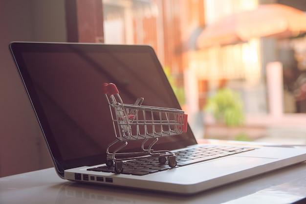 Online-shopping-konzept leerer einkaufswagen auf einer laptoptastatur Premium Fotos