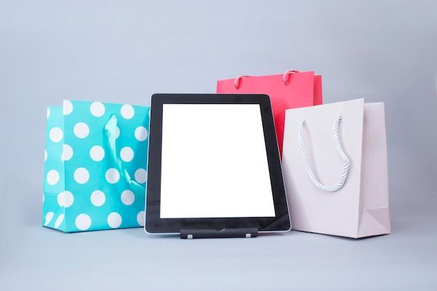 Online-shopping-konzept. nahaufnahme-tablettenmodell mit weißem bildschirm mit hellen geschenktüten auf grauer wand. Premium Fotos