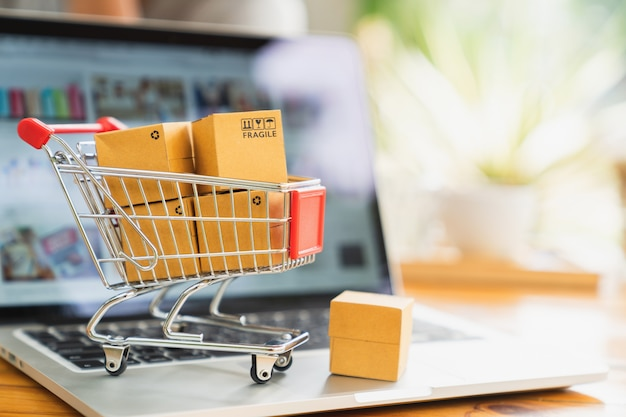 Online-shopping- und lieferungskonzept, produktpaket-boxen im warenkorb und laptop Premium Fotos