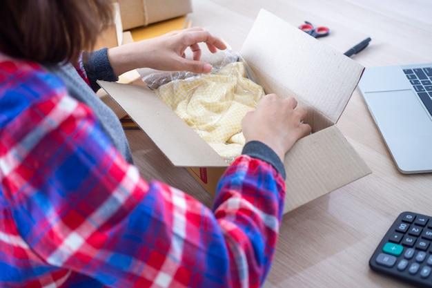 Online-verkäufer verpacken hemden in kartons, um produkte an käufer zu liefern, die auf der website bestellen Premium Fotos