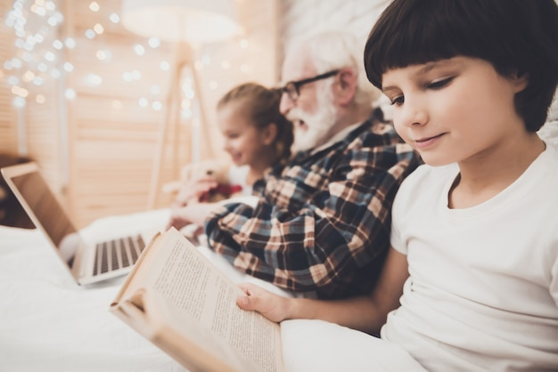 Opa und kinder lesen und schauen filme im bett. Premium Fotos