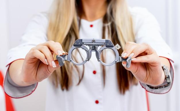 Ophthalmologischer versuchsrahmen und testbrille in frauenhänden Premium Fotos