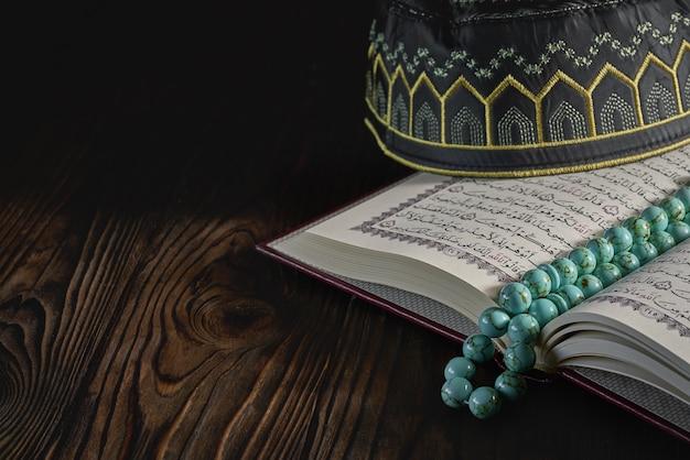 Opren islamisches buch koran mit rosenkranzperlen und kopiah-hut für muslime Premium Fotos