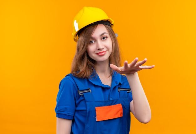Optimistische junge baumeisterin in bauuniform und schutzhelm, die nach entspannung fragt, nehmen es leicht und machen ruhegeste mit lächelnder hand Kostenlose Fotos