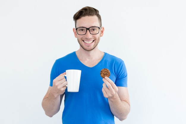 Optimistischer kerl trinkt kaffee mit keks Kostenlose Fotos