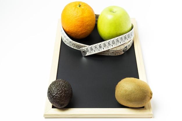 Orange, apfel, kiwi und avocado umgeben von einem maßband Premium Fotos