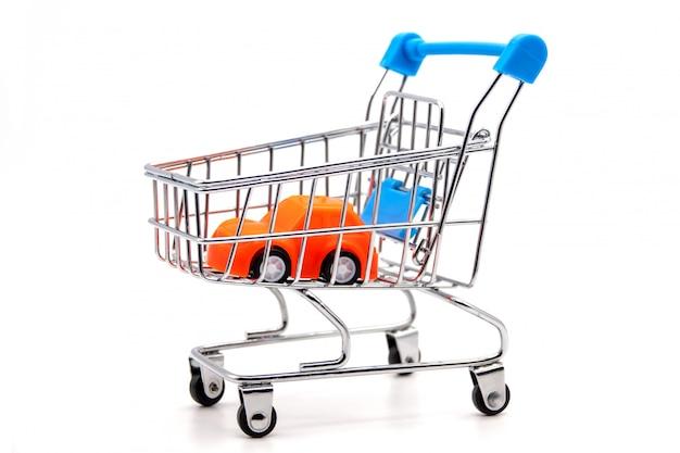Orange auto innerhalb eines kleinen einkaufswagens. Premium Fotos
