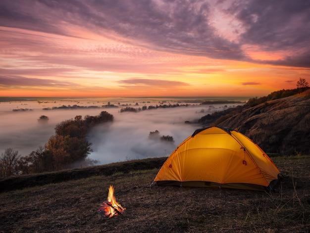 Orange beleuchtet im zelt und feuer über nebligen fluss bei sonnenuntergang Premium Fotos
