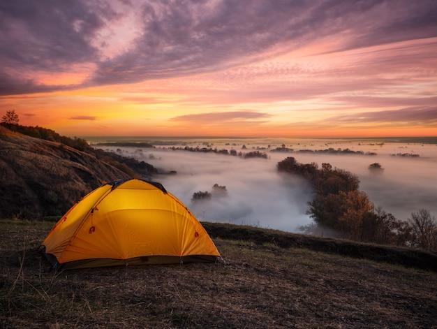 Orange beleuchtet von innen zelt über fluss bei sonnenuntergang Premium Fotos