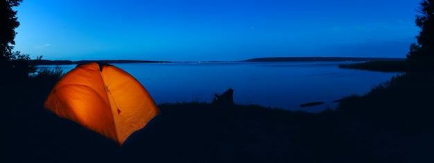 Orange beleuchtetes zelt am see Premium Fotos