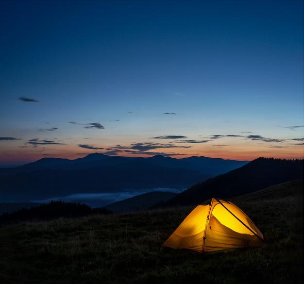 Orange beleuchtetes zelt in den bergen unter dem abendhimmel Premium Fotos