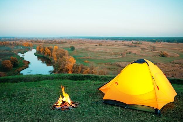 Orange beleuchtetes zelt und lagerfeuer auf einem hügel über dem fluss Premium Fotos