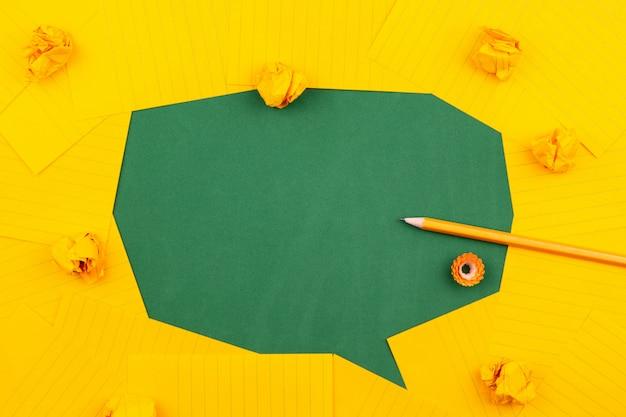 Orange blätter papier liegen auf einer grünen schulbehörde und bilden eine sprechblase mit bleistift, zerknitterten papieren und textfreiraum. Premium Fotos