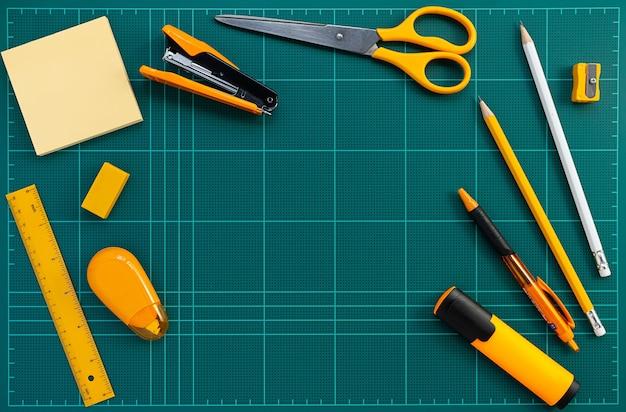 Orange briefpapierbüroartikel auf grüner schneidematte, flaches lagebild Premium Fotos