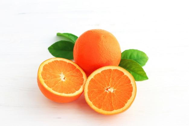 Orange frucht und man schnitten zur hälfte, wenn das blatt auf weißem hintergrund getrennt ist. Premium Fotos