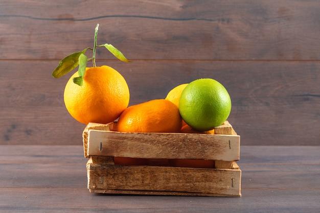 Orange fruchtmandarine und grüne zitrone in der holzkiste auf brauner oberfläche Kostenlose Fotos