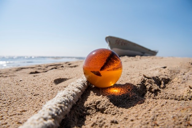 Orange glaskugel auf sand nahe dem meer Premium Fotos