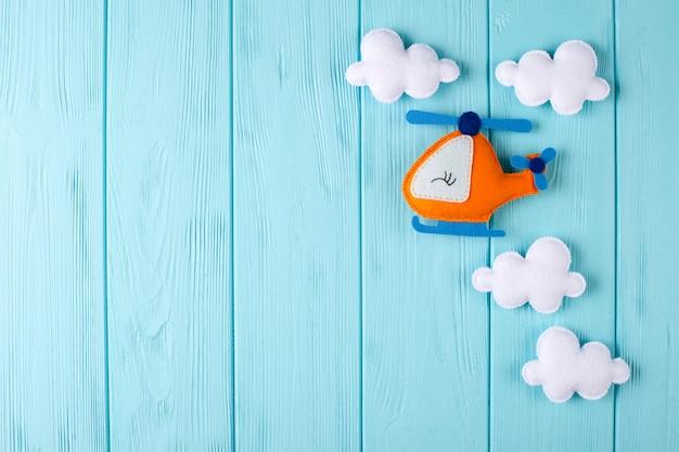 Orange handwerkshubschrauber und -wolken auf blauem hölzernem hintergrund mit copyspace. filz handgefertigte spielzeug. Premium Fotos