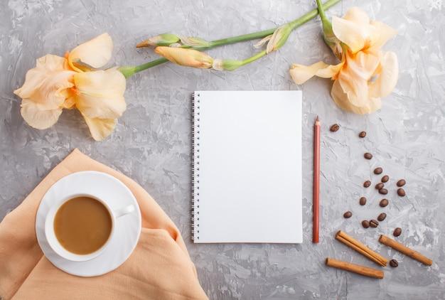 Orange irisblumen und ein tasse kaffee mit notizbuch auf grauem beton Premium Fotos