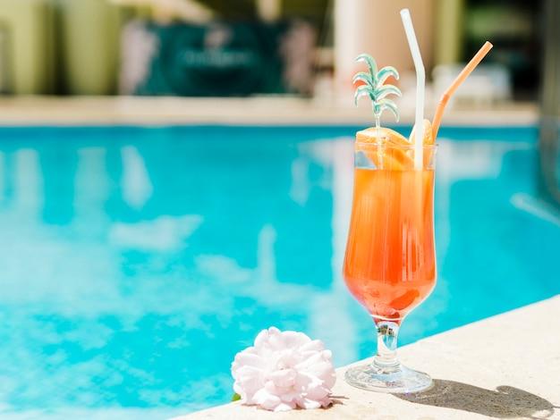 Orange kaltes cocktail nahe pool Premium Fotos