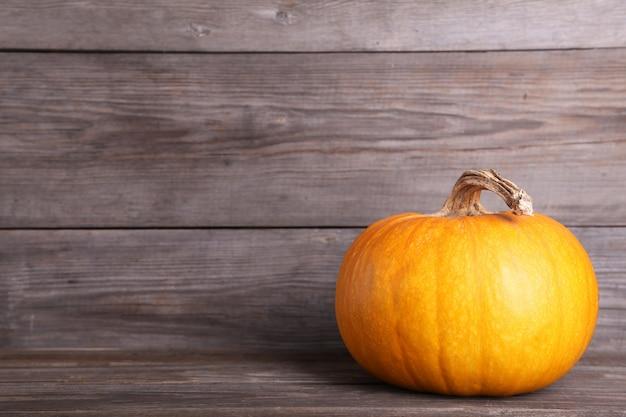 Orange kürbis auf einem grauen hintergrund. herbst Premium Fotos
