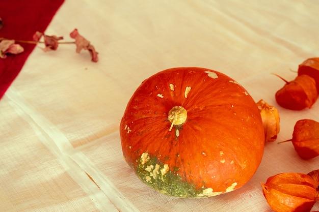 Orange kürbise auf einer tabelle bedeckt mit leinentischdecke Premium Fotos