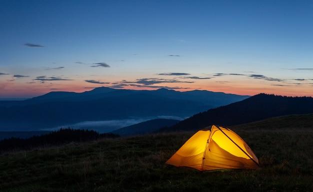Orange leuchtendes zelt am berg am abend oder am frühen morgen Premium Fotos