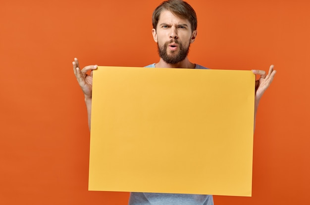 Orange marketingblatt des männlichen marketingplakatwerbemodells Premium Fotos