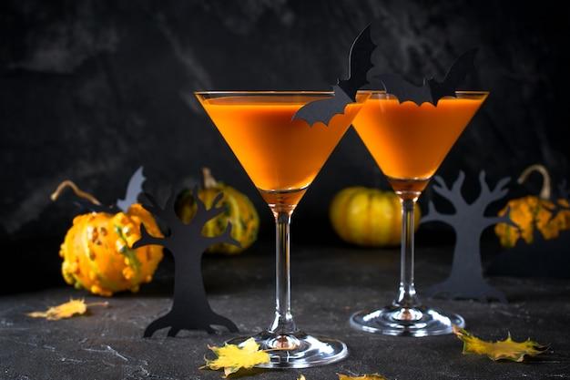 Orange martini cocktails mit fledermäusen und dekor für halloween-party, auf dunklem hintergrund Premium Fotos