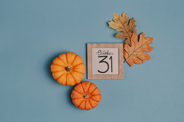 Orange minikürbise und kalenderdatum im holzrahmen Premium Fotos
