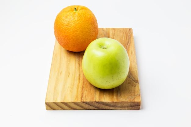 Orange und apfel auf einem holzbrett Premium Fotos