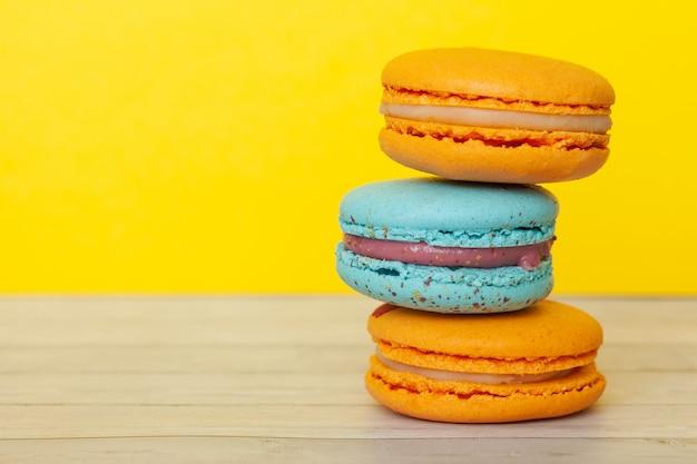 Orange und blaue makronen, französische plätzchen als festlichkeit für den feiertag Premium Fotos