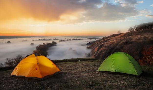 Orange und grüne zelte über dem vom nebel geschützten fluss Premium Fotos