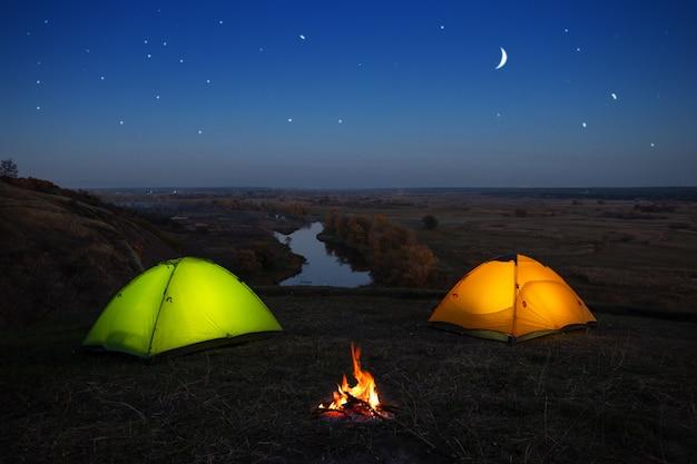 Orange und grünes zelt am fluss in der nacht Premium Fotos