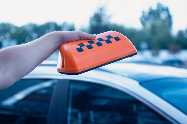 Orange zeichen eines taxis in den händen eines mannes Premium Fotos