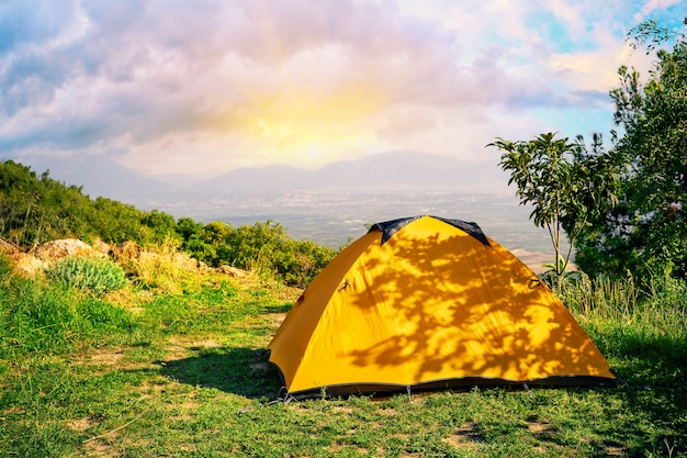 Orange zelt auf einem hügel mit bergen im hintergrund bei sonnenaufgang Premium Fotos